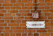 Design-Tapete mit Ziegelmauer – Feuermelder an der Hauswand