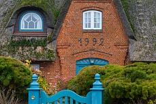 Wunderschönes Reetdachhaus mit blauen Elementen und blauen Tor in Sylt