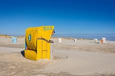 Leuchtend gelber Strandkorb auf Amrum
